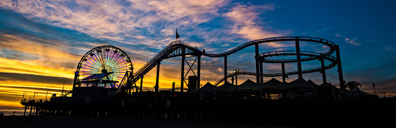 Roller coaster and ferris wheel at sunset